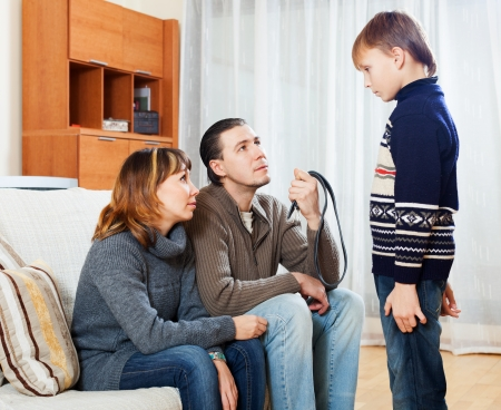 Mother and  father with belt scolding teenager son at home photo
