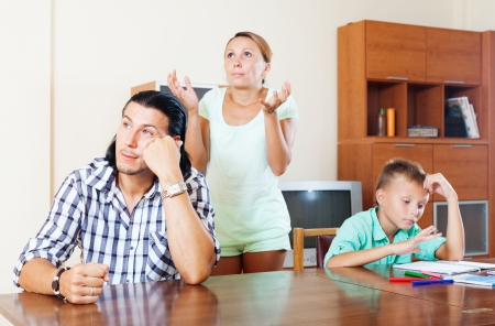 Ordinary family of three with teenager boy having quarrel in living room photo