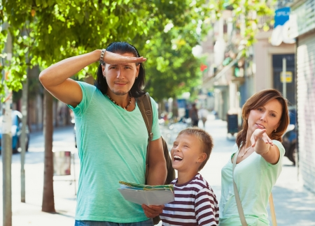 Woman pointing the direction for family at city photo
