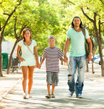 Happy family of three with teenager walking in summer park photo