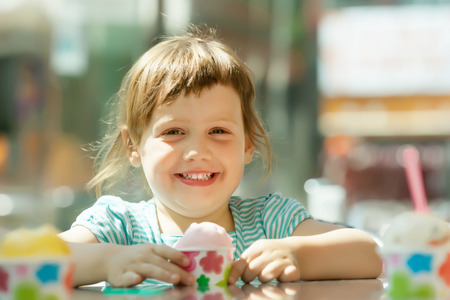 Happy 3 years baby girl eating ice cream at outdoor cafe in summer photo