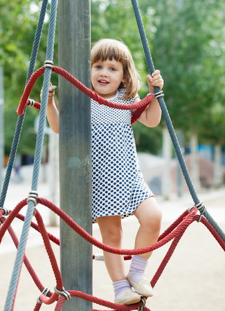 adroitness: Smiling child climbing at ropes on playground area in summer Stock Photo