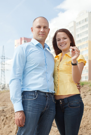 homeownership: Happy couple with key against new brick house    Stock Photo