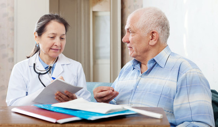 auscultoscope: Mature doctor and seniormale  patient near table with documents
