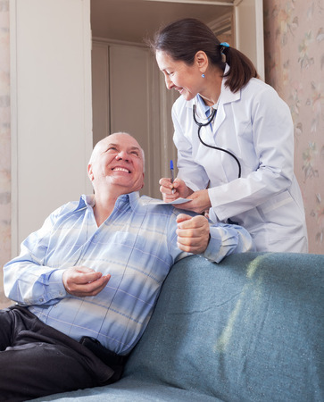 malaise: Happy senior man tells the mature doctor the symptoms of malaise on couch