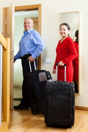 mature couple with luggage in home going on vacation photo