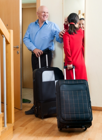 Happy mature couple with luggage looking in mirror near door going on holiday photo