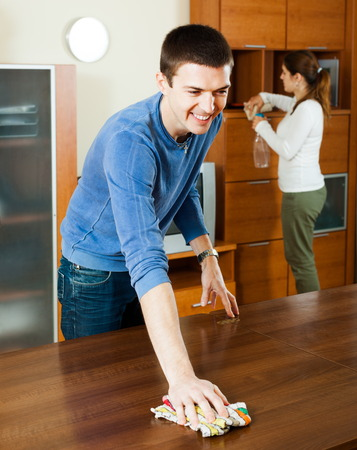 Happy man with wife dusting wooden furniture at living room photo