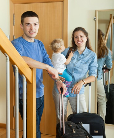 middle-aged couple with toddler with suitcases near door at home photo