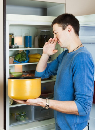 frowy: Hungry man holding foul food near refrigerator