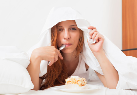 furtively: Young woman eating sweet cake under sheet in bed Stock Photo