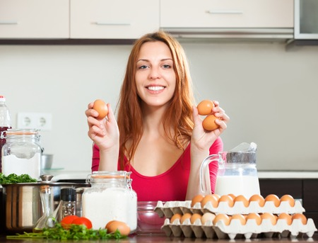 Smiling girl in red cooking omelet with eggs in home kitchen photo