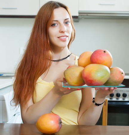 ordinary woman: ordinary woman holding plate with ripe mango at home kitchen  Stock Photo