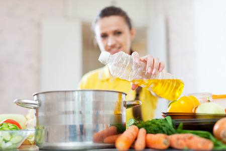 pours: Woman in yellow pours oil from bottle into the pan. Focus on bottle Stock Photo