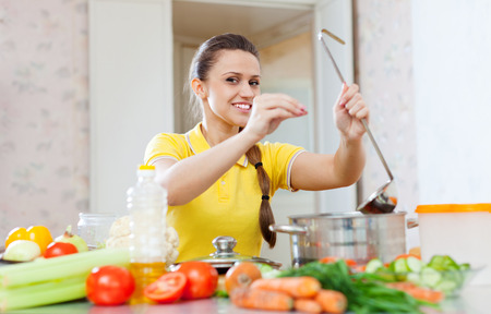 beautiful young woman adds spice or salt in saucepan at kitchen photo