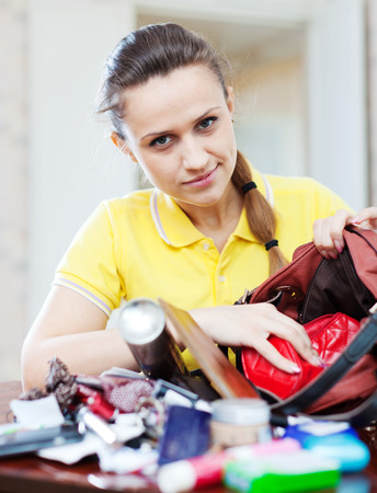 preoccupation: inconsiderate woman lost something and searching in handbag Stock Photo