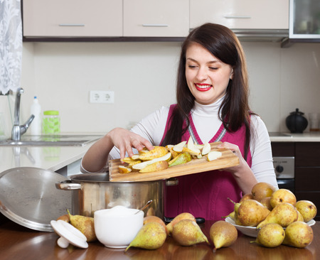 Brunette woman cooking pear jam  in kitchen photo