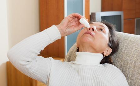nasal drops: Mature woman dripping nasal drops in home