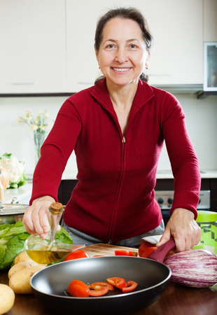 mature woman pouring oil to frying-pan at home photo