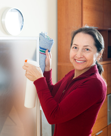 Smiling mature woman cleaning  glass with rag and cleanser photo