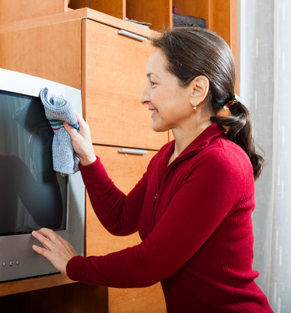 Ordinary mature woman cleaning TV at living room photo