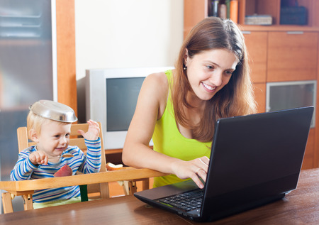 disgruntled: mother working at home with baby