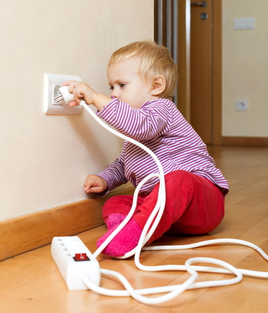 toddler playing with electricity at home photo