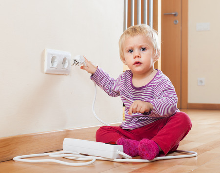 Baby playing with electrical extension and outlet on floor   photo