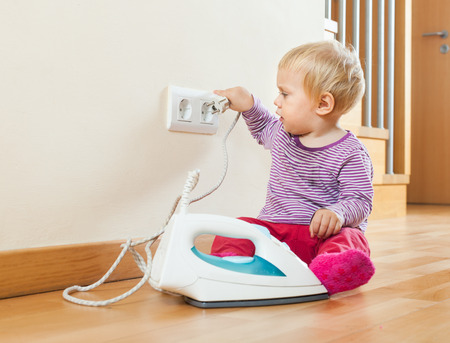 Toddler playing with electric iron on floor at home photo