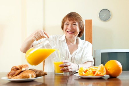 eating breakfast: Positive mature woman having breakfast with juice in morning