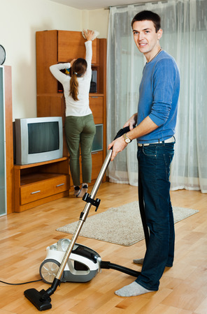 vaccuum: Adult man with wife doing housework together in home Stock Photo