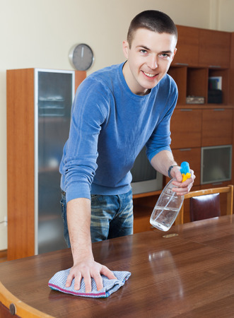 Smiling man cleaning furniture with cleanser and rag at living room photo