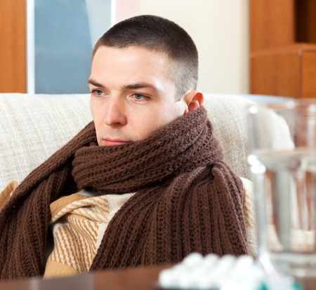 ill sad man in warm scarf at home Stock Photo