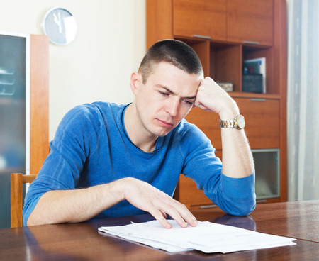 parsimony: Sad young man looking at financial documents in frustration sitting at table Stock Photo