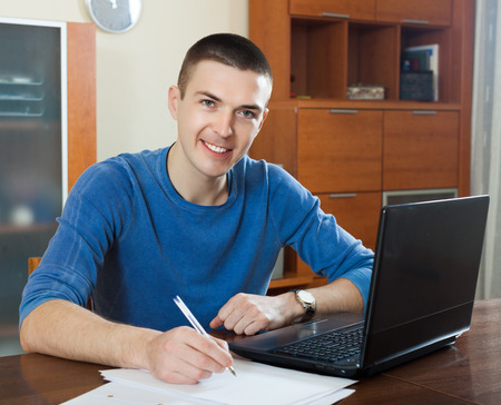 parsimony: Smiling man  staring financial documents in home interior Stock Photo