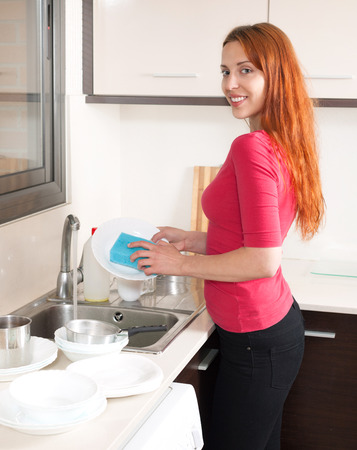 Smiling pretty red haired woman washing dishes in the kitchen at home  photo