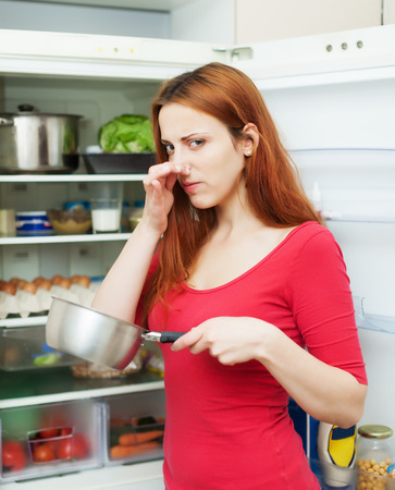 frowy: Long-haired  woman  in red holding  nose because of bad smell near fridge at home