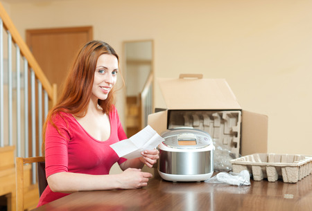 Happy smiling young  housewife unpacking new multicooker in home in living room  photo