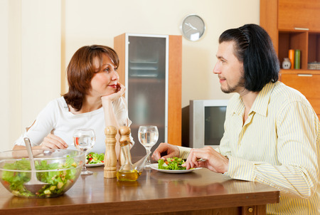 Happy couple eating juicy vegetables and herbs in the home   photo
