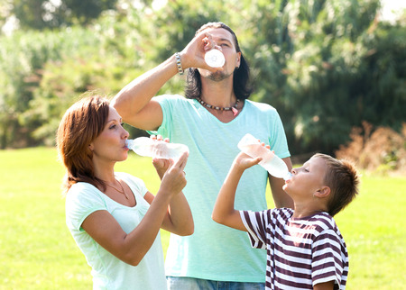 Happy parents with son drinking from plastic bottles in summer park photo