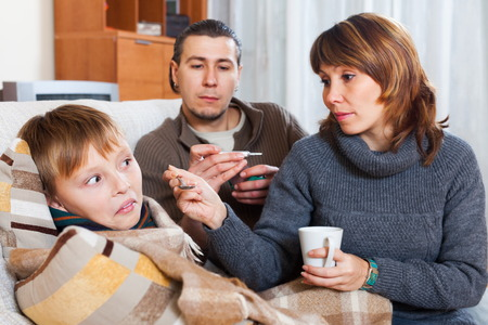 nosotrophy: Adult couple and sick boy with thermometer at home Stock Photo