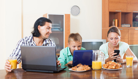 Happy  family looking e-mail in laptops during breakfast time at home  photo