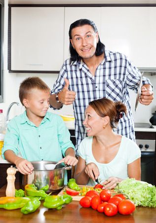 Happy family with teenager son cooking with fresh vegetables at home kitchen photo