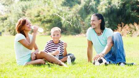 Happy parents with child drinking from plastic bottles in summer park photo