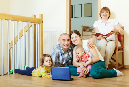 happy multigeneration family with two children with laptop on floor at home photo