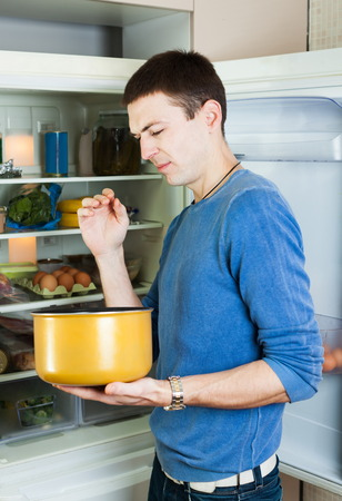 Hungry man with foul food near refrigerator at home photo
