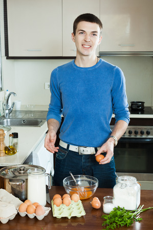 Guy cooking scrambled eggs in home kitchen photo