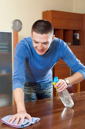 cleanser: Happy man dusting wooden table with rag and cleanser at home