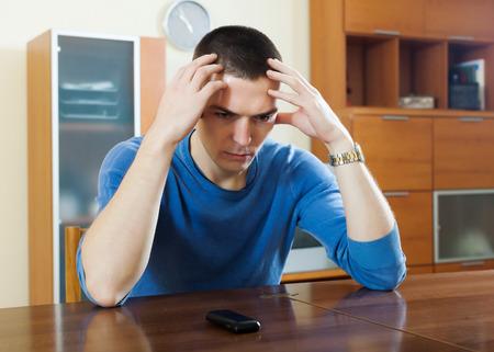 desilusion: Hombre que tiene decepci�n despu�s de la llamada de tel�fono en casa