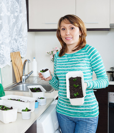 Smiling woman in green with  seedlings in domestic kitchen photo